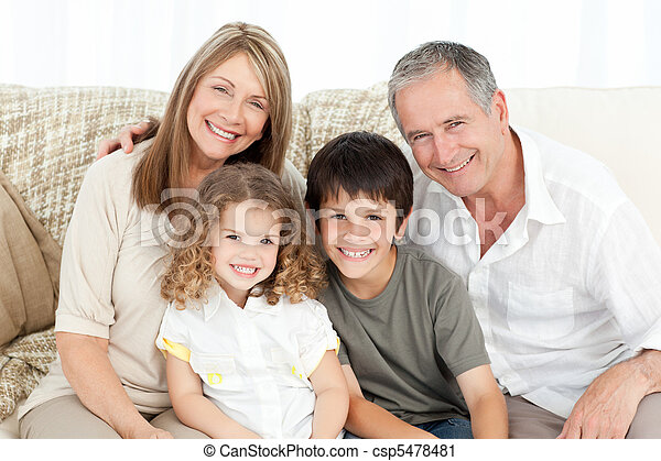 A happy family on their sofa looking at the camera - csp5478481
