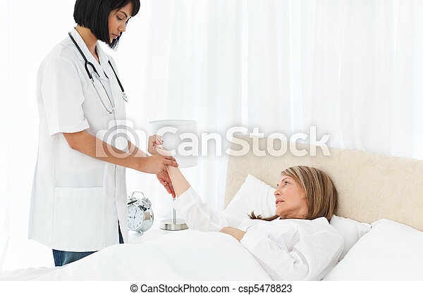 Nurse taking the pulse of her patient - csp5478823
