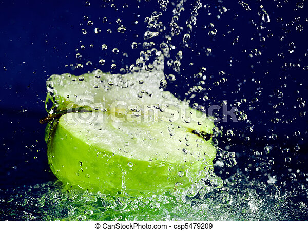 Half of green apple with stopped motion water drops on deep blue