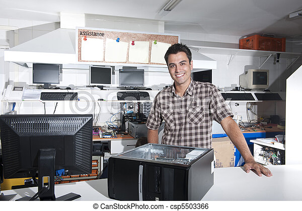 Happy owner of a computer repair store - csp5503366