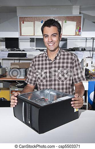 Happy owner of a computer repair store - csp5503371