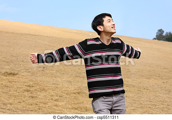Carefree man standing in golden grass field being happy enjoying freetime  - csp5511311