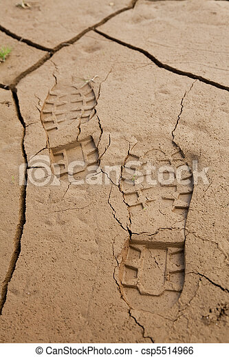 Boot Footprints in Dry Cracked Earth - csp5514966
