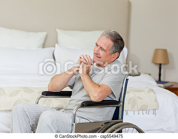 Smiling senior man in his wheelchair  at home - csp5549475