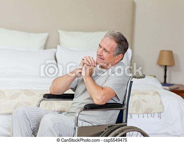 Smiling senior man in his wheelchair  at home - csp5549475