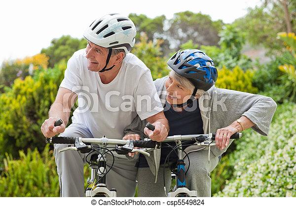 Mature couple mountain biking outside - csp5549824