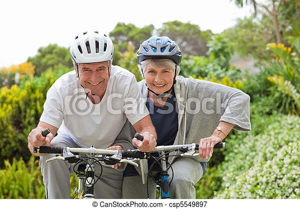 Mature couple mountain biking outside - csp5549897