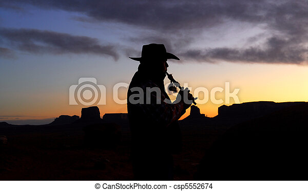 Navajo Native American Indian playing flute at sunrise - csp5552674