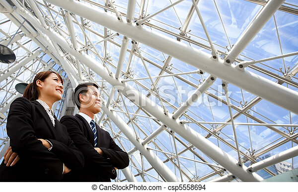 two business people stand in modern office - csp5558694