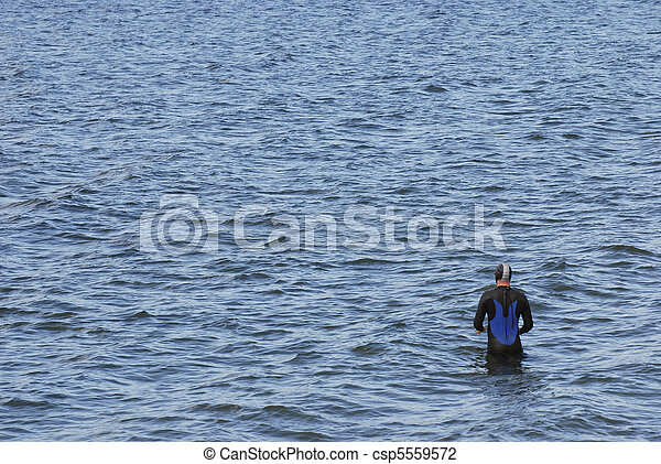 Man in wetsuit preparing to swim - csp5559572