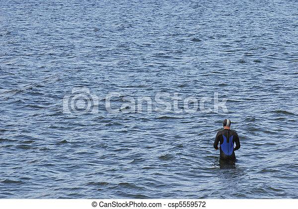 Man in wetsuit preparing to swim - csp5559572