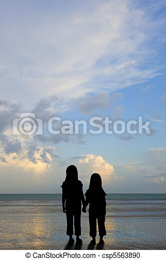 Silhouette vulnerable kids on sunset beach - csp5563890