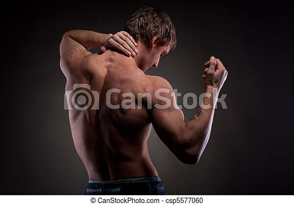 Muscular naked man from back on black - csp5577060
