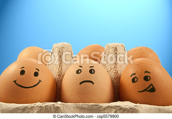 Close and low level of several brown eggs with painted faces against blue light effect background