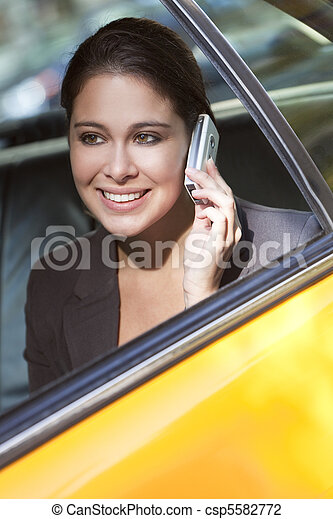 Young Woman Talking on Cell Phone in Yellow Taxi - csp5582772