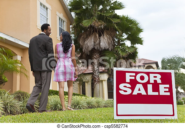 African American Couple Beside House For Sale Sign - csp5582774