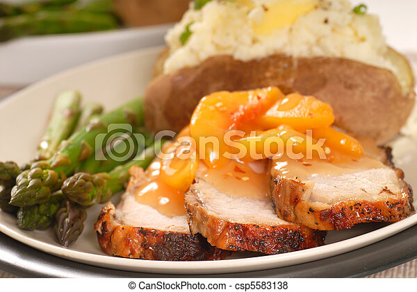 Cooked pork with a peach sauce with baked potato and asparagus - csp5583138