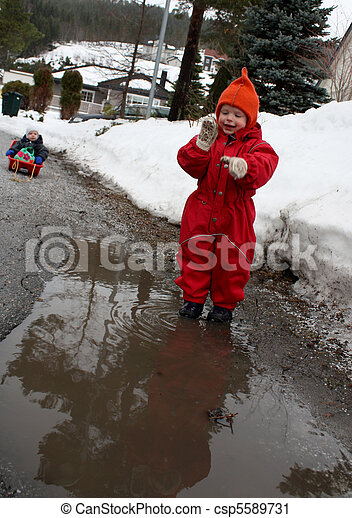 Children playing in the mud in early spring - csp5589731