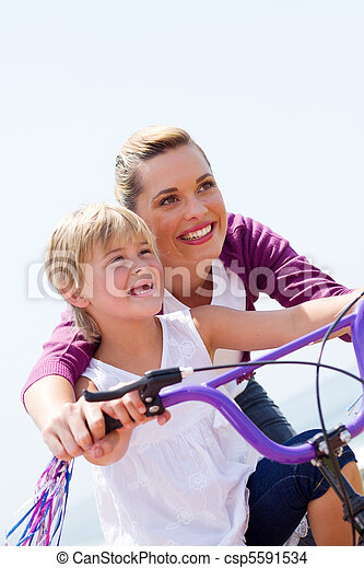 happy mother teaching girl bicycle - csp5591534