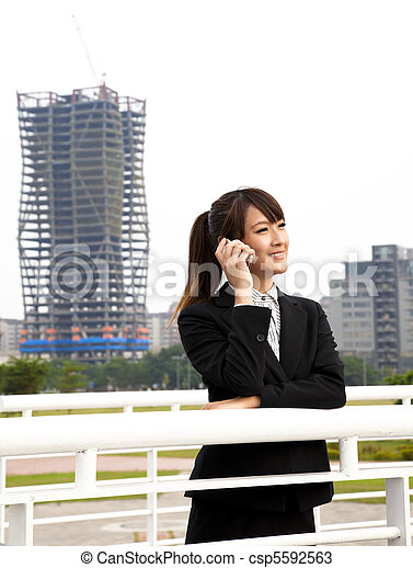 Happy asian business woman talking on the phone and office building background - csp5592563