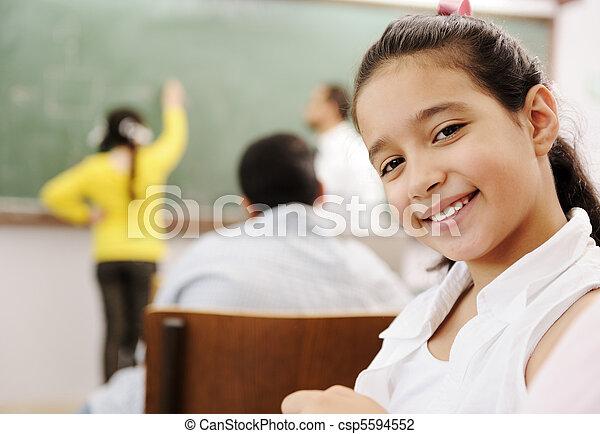 Adorable girl smiling in school classroom and behind her class activities - csp5594552