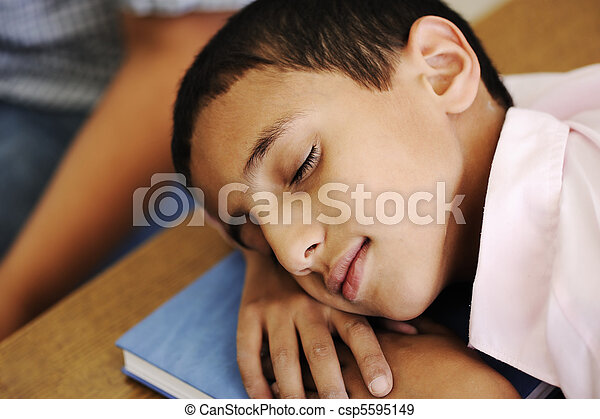 Kid in classroom on desk falling asleep on his notebook - csp5595149