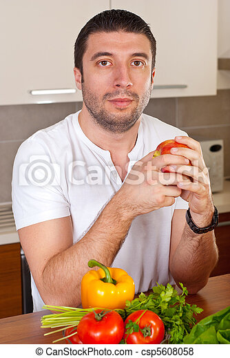 Mid adult man holding apple in kitchen - csp5608058