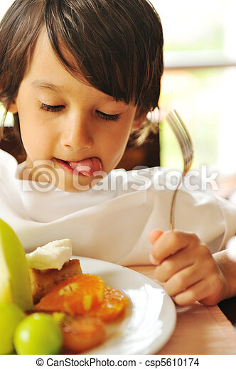 Real enjoying food, cute kid with finger in his mouth - csp5610174