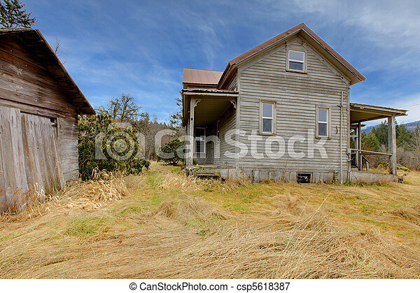 Very old grey house and shed on the farm land - csp5618387