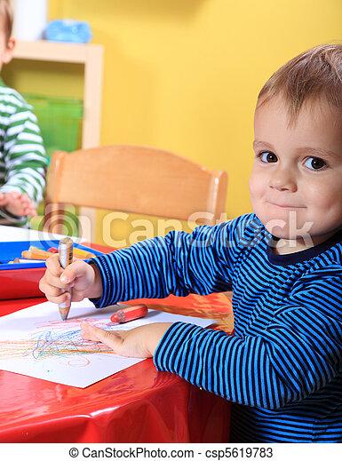Toddler drawing in kindergarten - csp5619783