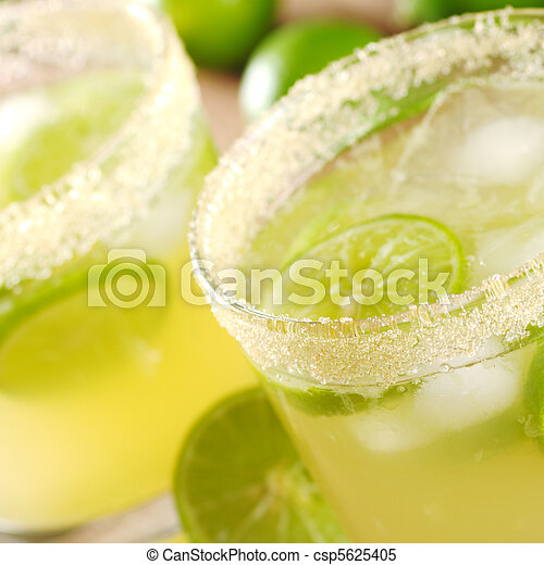 Fresh lemonade with lime slices and ice cubes in a sugar rimmed glass (Very Shallow Depth of Field, Focus on the sugar rim of the first glass) - csp5625405