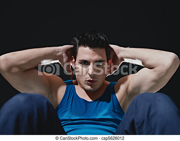 man doing series of sit-ups on black background - csp5626012