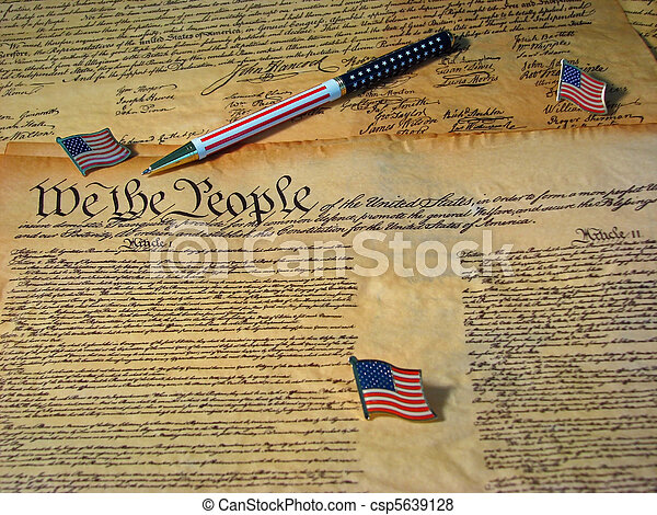 A copy of the Constitution of the United States resting on a copy of the Declaration of Independence accompanied by flags and a flag pen. - csp5639128