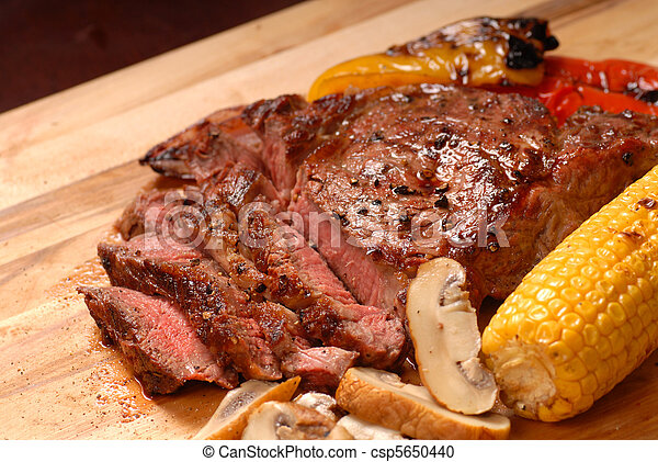 A sliced grilled BBQ ribeye steak with vegetables - csp5650440