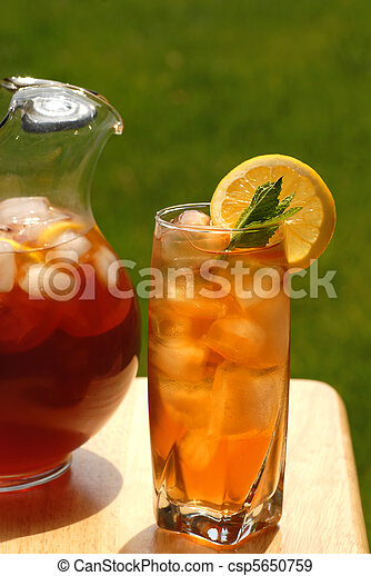 Glass of iced tea with pitcher of tea next to it - csp5650759