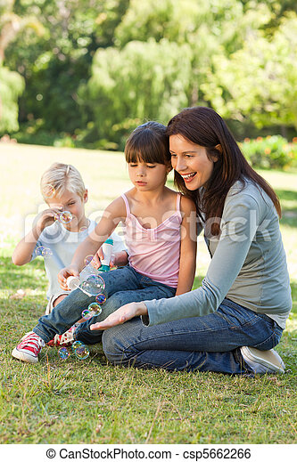 Family blowing bubbles in the park - csp5662266