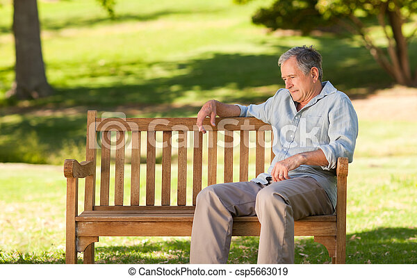 Elderly man sitting on a bench - csp5663019