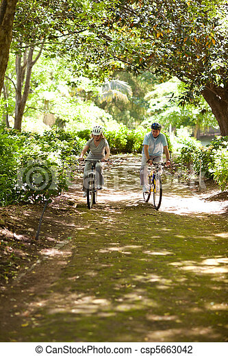 Elderly couple mountain biking outs - csp5663042