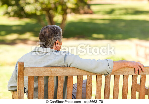 Elderly man sitting on the bench with his back to the camera - csp5663170