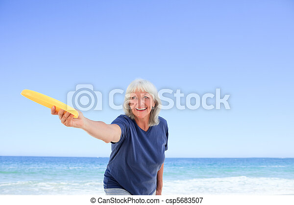 Elderly woman playing freesby - csp5683507