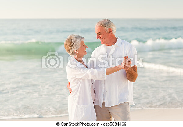 Elderly couple dancing on the beach - csp5684469