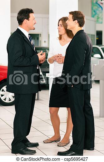 Couple with salesman at car dealer - csp5695427
