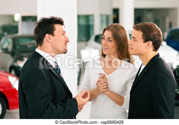 Couple with salesman at car dealer - csp5695428