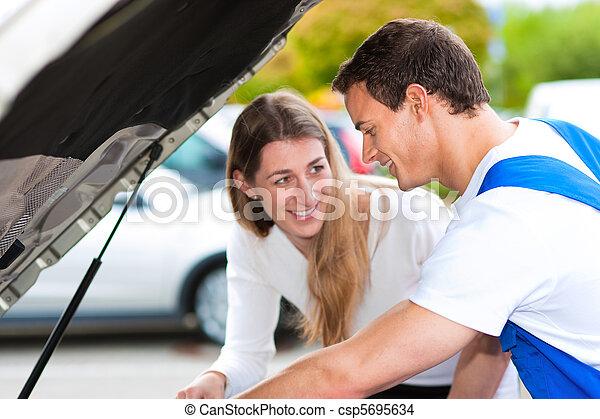 Woman talking to car mechanic in repair shop - csp5695634