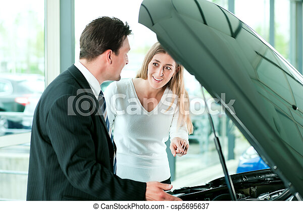 Woman buying car from salesperson - csp5695637