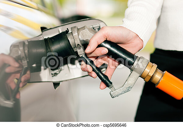 Woman refueling car with LPG gas - csp5695646
