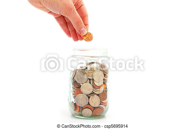 hand putting penny in a coin jar, saving money - csp5695914
