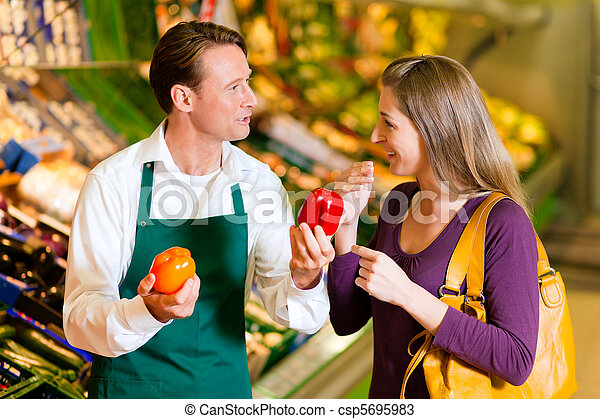 Woman in supermarket and shop assistant - csp5695983