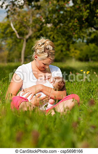 Mother nursing baby on meadow - csp5698166