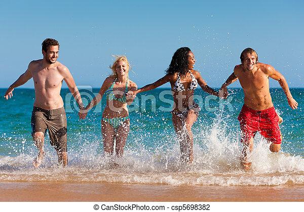 Friends running on beach vacation - csp5698382